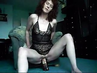 Mature Lady Swallows A Whisky Bottle